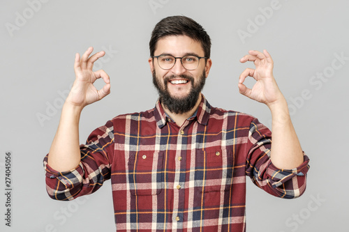Valokuva  Portrait of handsome excited man smiling and showing ok sign