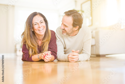 Stampa su Tela  Beautiful romantic couple sitting together on the floor at home
