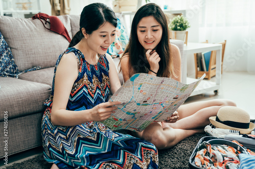 Photo  Two beautiful asian women planning trip helping to prepare luggage to travel abroad on floor