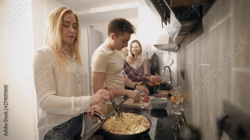 Fotografie, Obraz  young people are cooking together in modern kitchen, two women are washing veget
