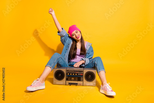 Full length body size photo beautiful she her lady weekend vacation leisure vintage audio recorder sit floor funky wear casual jeans denim jacket shoes pink hat isolated yellow vivid bright background - 274053652