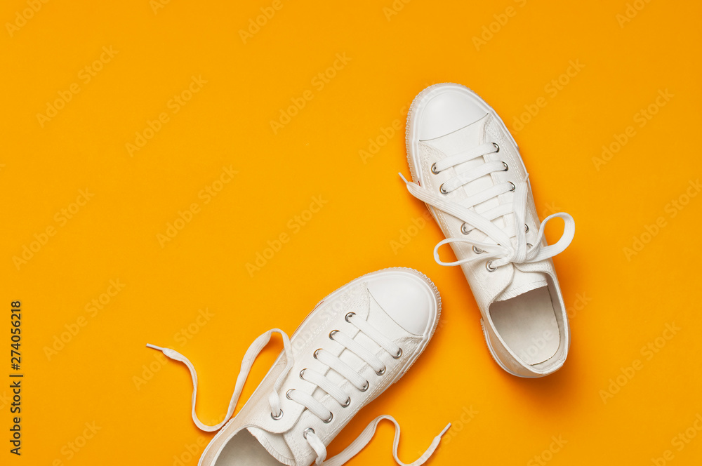 Fototapety, obrazy: White female fashion sneakers on yellow orange background. Flat lay top view copy space. Women's shoes. Stylish white sneakers. Fashion blog or magazine concept. Minimalistic shoe background, sport