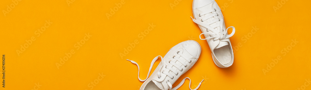 Fototapeta White female fashion sneakers on yellow orange background. Flat lay top view copy space. Women's shoes. Stylish white sneakers. Fashion blog or magazine concept. Minimalistic shoe background, sport