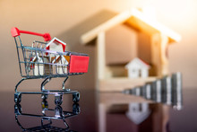 Buying Property Or Real Estate Investment Concept. Home Mortgage And Lease. Bank Loan Interest Rate. Wooden House Models In Mini Shopping Cart With Step Of Coins Stacked On Glossy Table.