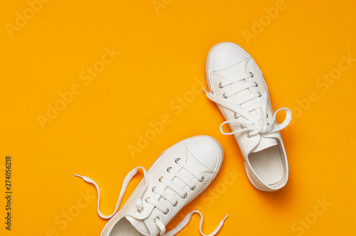 Fotografia  White female fashion sneakers on yellow orange background