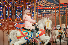 Adorable Smiling Caucasian Child Girl Riding On Merry Go Round Carousel Horse At Christmas Winter Market Outdoor. Happy Child Having Fun Celebrating New Year.