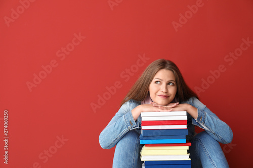 Beautiful young woman with books on color background Canvas Print