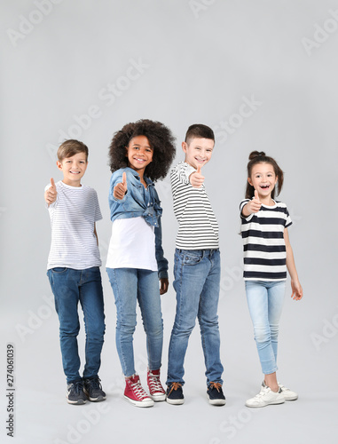 Vászonkép Stylish children in jeans showing thumb-up gesture on grey background