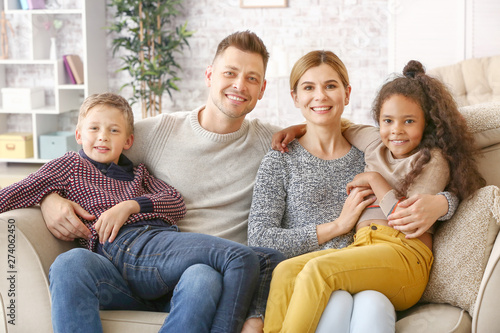 Photo Happy couple with little adopted children at home