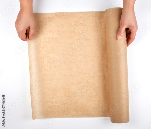 Valokuvatapetti roll of brown parchment paper for baking food in female hands
