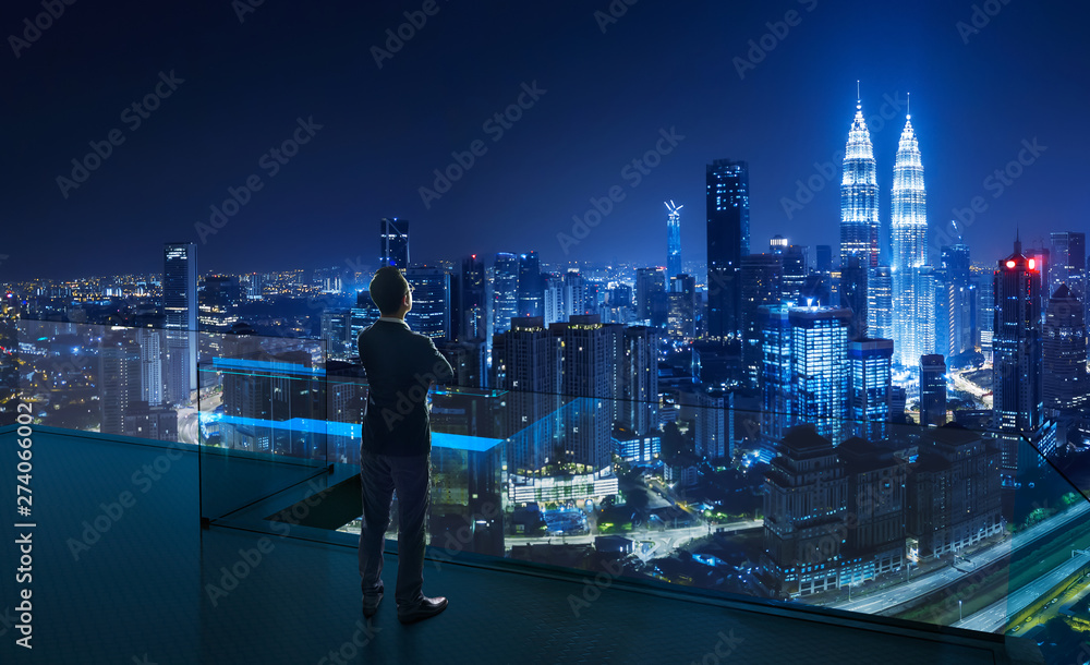 Fototapeta Businessman standing on open roof top balcony watching city night view . Business ambition and vision concept .