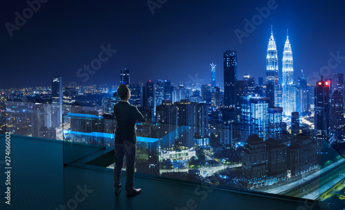Businessman standing on open roof top balcony watching city night view Canvas Print