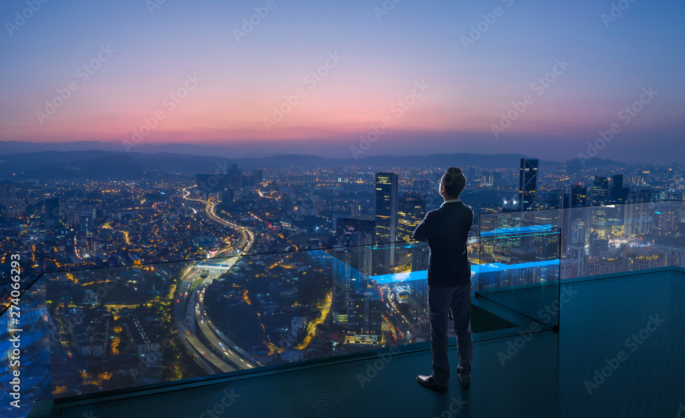 Fototapety, obrazy: Businessman standing on open roof top balcony watching city night view . Business ambition and vision concept .