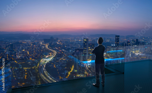 Obraz na plátne  Businessman standing on open roof top balcony watching city night view