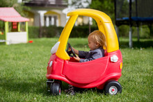 Cute Toddler Boy, Riding Big Plastic Red Car Toy In The Park