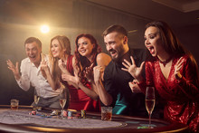 Group Of A Young Rich Friends Are Playing Poker In Casino.