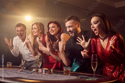 Fotografie, Obraz  Group of a young rich friends are playing poker in casino.