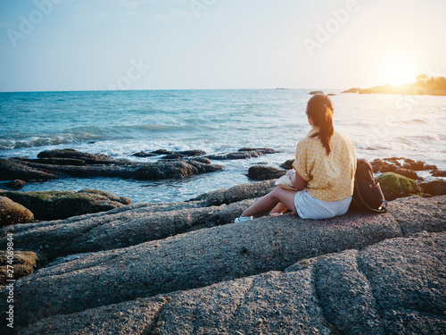 Photo sur Aluminium Detente Woman looking to the sea and sitting on the rock. Hipster woman travel at the beach.
