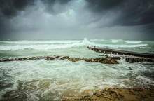 Stormy Sea Waves Crashing Into Wooden Pier And Big Dark Grey Storm Clouds Approaching
