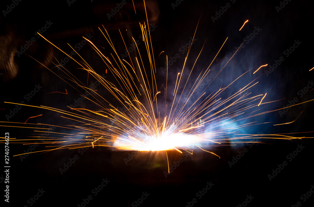 Fototapety, obrazy: Sparks from welding at a construction site as a background