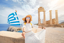 Woman Traveler With Backpack Enjoying Great View Og The Ancient Greek Acropolis With Flag In Hands