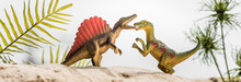 Selective Focus Of Toy Dinosaurs Roaring On Sand Dune With Tropical Leaves, Panoramic Shot