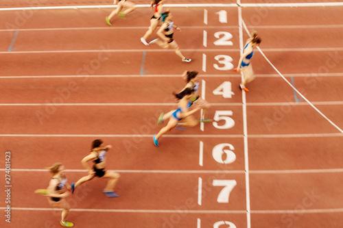 Fototapeta finish line woman runners sprinters run 100 meters motion blur