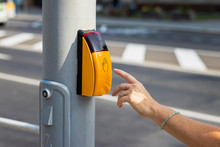 Woman Hand Pressing Crosswalk Button To Cross The Road. Crossing Street Safely.