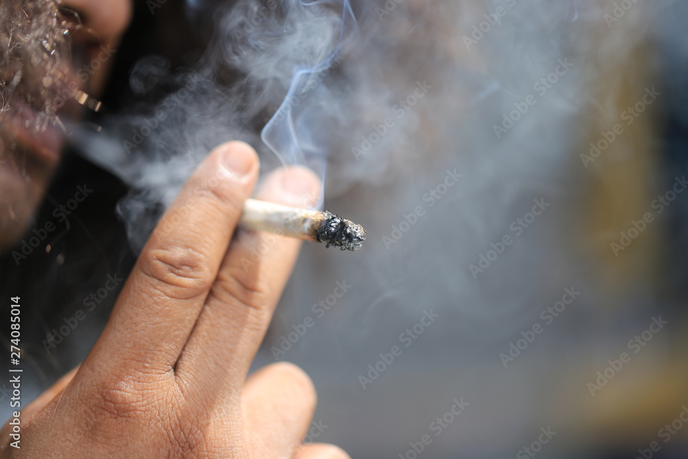 Fototapety, obrazy: Bearded man smoking a marijuana cannabis joint or smokes a cigarette on green background, Medical marijuana should not be used in illegal ways, Stop smoking concept