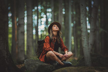 Style Girl With Backpack Sitting In A Stone In A Summer Time Mixed Coniferous Forest