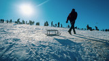Bansko, Bulgaria - circa Jan, 2018: Boy sledge on snow with crowd of people enjoying the popular winter recreation centar Bansko in Bulgaria