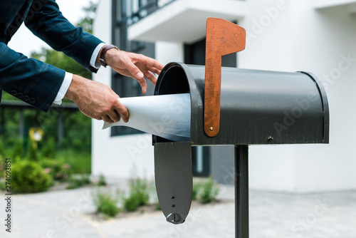 Fototapeta  cropped view of man putting blank paper in mail box near house