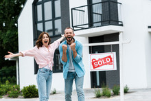 Cheerful Man And Woman Celebrating Near House And Board With Sold Letters