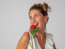 Plays, Touches And Smells A Red Rose In A Photographic Studio