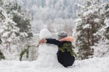 Rear View Of Little Girl Sits In Embracing One Another With A Snowman In Winter Snowy Park.