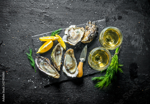 Papel de parede Fresh raw oysters on a stone Board with white wine.