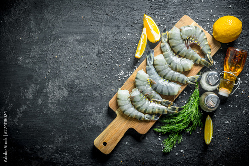 Photo  Raw shrimps on a cutting Board with lemon slices, spices and dill
