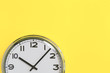 canvas print picture - Part of analogue plain wall clock on trendy yellow background. Ten o'clock. Close up with copy space, time management or school concept and lunch time