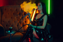 Sexy Brunette Model Is Smoking A Hookah Exhaling A Smoke At A Luxury Night Club.