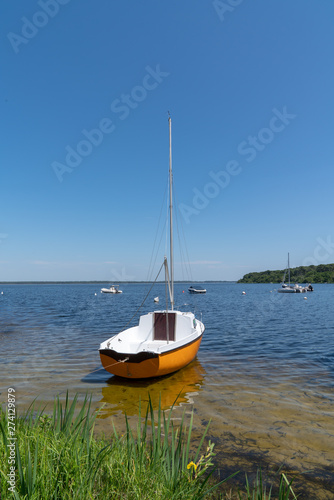 single boat orange and white in blue water lake in Lacanau Gironde in France