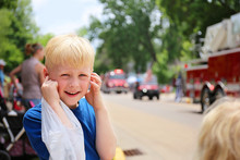 Cute Boy Child At Parade Plugging His Ears From The Loud Fire Truck Sirens