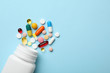 canvas print picture - Bottle and scattered pills on color background, top view. Space for text