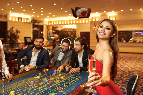 Photo  A woman with glass of champagne in a dress at table roulette in casino