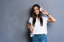 Smiling Woman Listening Music In Headphones And Using Smartphone Over Gray Background.