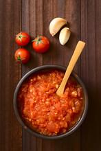 Homemade Traditional Italian Marinara Or Pomodoro Tomato Sauce Made Of Fresh Tomato, Garlic, Dried Oregano And Salt, Photographed Overhead On Dark Wood With Natural Light