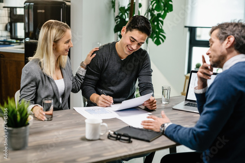 Fototapety, obrazy: Happy couple signing a contract while having meeting with real estate agent.