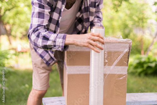 Valokuvatapetti stretch wrap roll, man packing the box for shipping