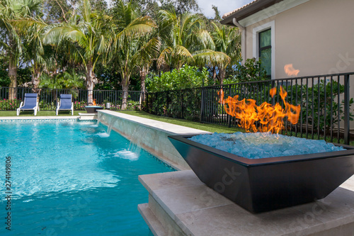 Gas fire pit next to a pool with waterfall Canvas Print