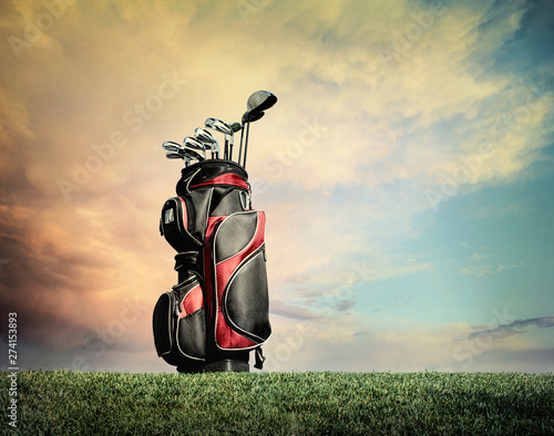Foto  Golf clubs on grass against dramatic clouds