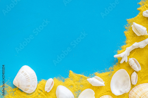Poster Fleur Shells on sand for beach pattern on blue background top view space for text